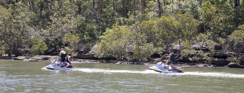 People driving two jetskies on a river