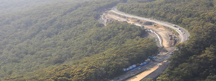Aerial photo of roadwork site of Picton Road reverse curves surrounded by bushland