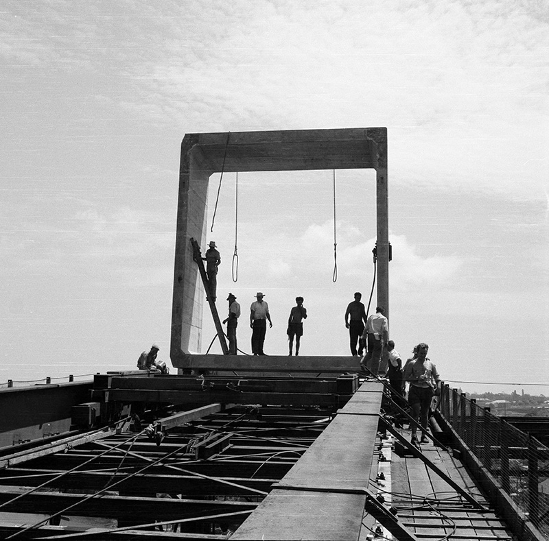 Workers stand inside a precast concrete segment as it is fixed to the bridge