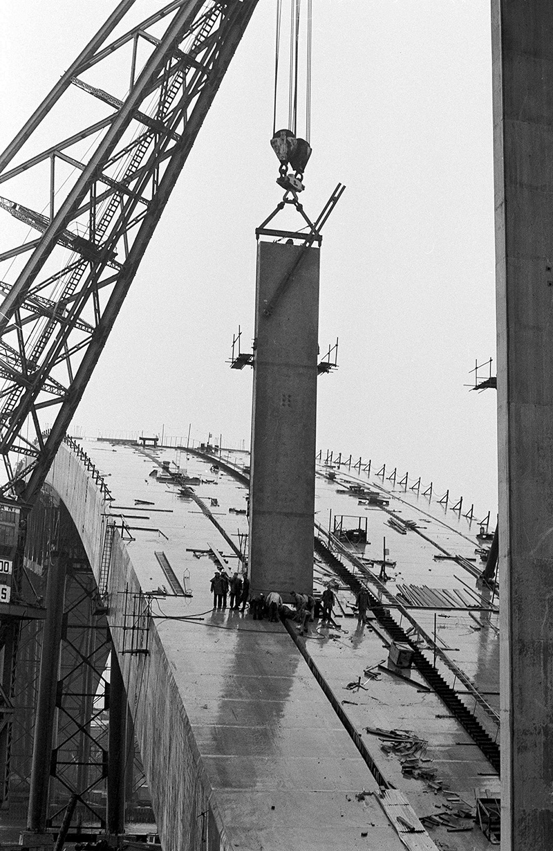 Workers guide a vertical panel as it is craned into position during construction