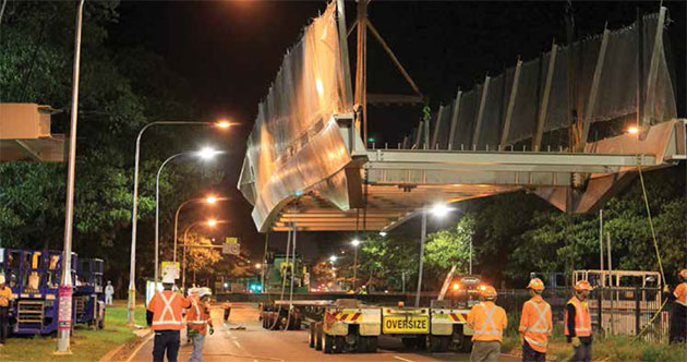 Workers at night look on as a large section of a bridge is craned into position from an oversize vehicle. Workers are all wearing Personal Protective Equipment (PPE), including hard hats and high-visibility reflective clothing.