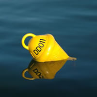 Yellow marker buoy floating in the water with the mooring number shown in black lettering.