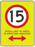 Yellow sign with black number 15 inside red circle and text 'speed limit in knots beyond this point'