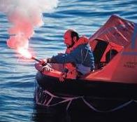 Image showing man leaning out of lifeboat holding a lit flare.