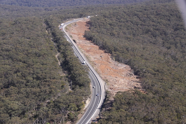 Aerial photo of reverse curves snaking through bushland with a large cleared area beside the road