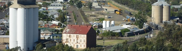 Gunnedah, showing the railway line and current level crossing at bottom right. Silos and industrial building are in the foreground.