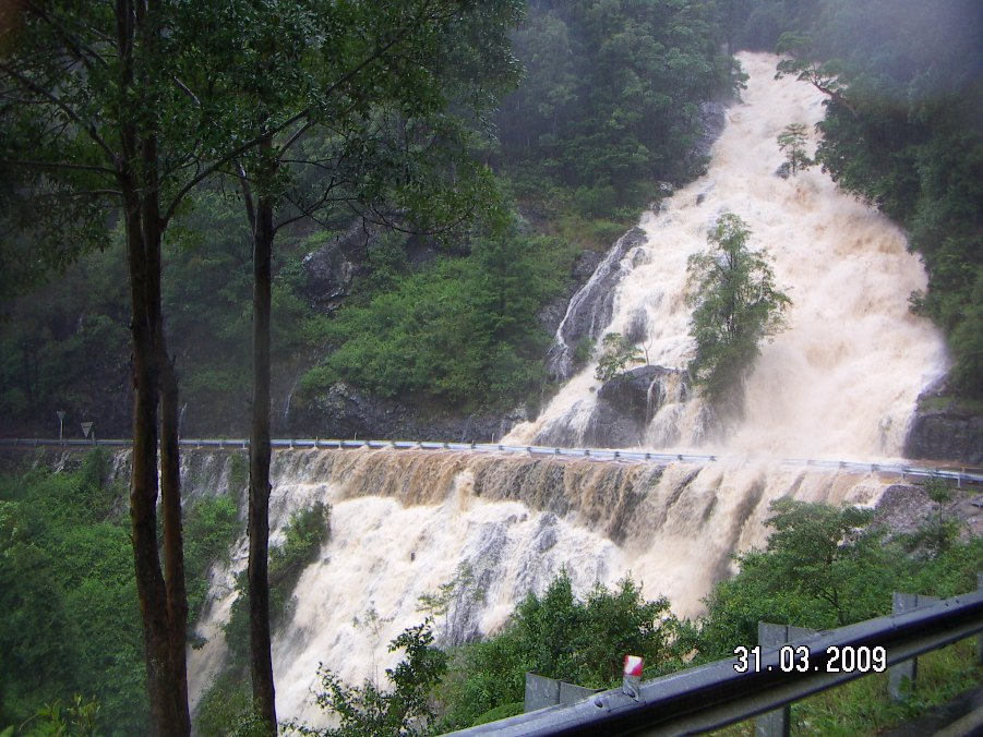 Flooding on Dorrigo Mountain in 2009 - a torrent of water flows down the slope and across the roadway