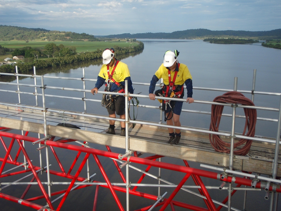 Maintenance workers in safety harnesses and helmets standing on scaffolding above the Harwood Bridge.