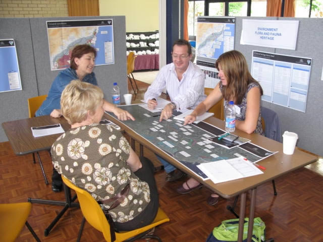 four people look at a map on a table at the information session