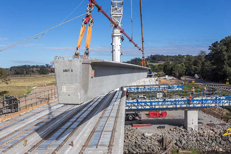 Placing a Super T girder on Broughton Creek bridge site number 1 (July 2015)