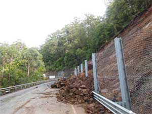 Rocks spilling through a barrier fence onto the highway at Clyde Mountain due to a landslip.