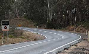 Part of the highway at between River Forest Road and the Mongarlowe River, showing a sharp left-hand bend through a heavily forested area, and a state 'Black Spots' traffic sign.