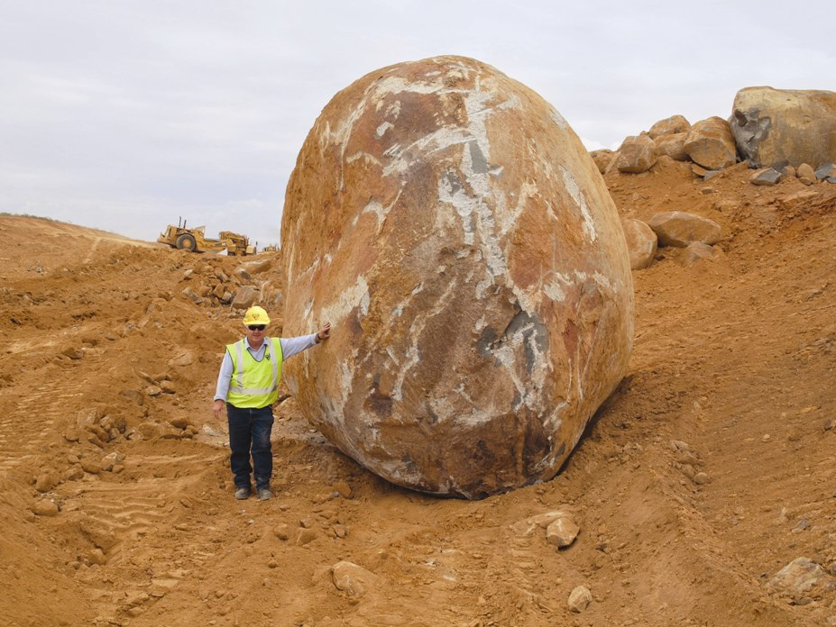 Worker in high-visibility vest and helmet leaning on a boulder twice his size at the Gounyan Curves worksite.