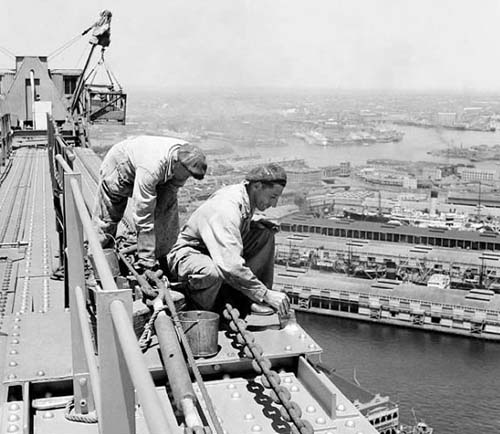 Two painters wearing overalls but no harness or safety equiment are painting the bridge in 1949