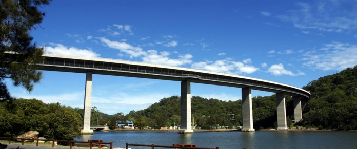 Woronora Bridge, looking from a low angle from the Woronora River, emphasising the height of the bridge above the water. Clearly visible are the five support pillars and the pedestrian/cyclepath slung under the road deck.