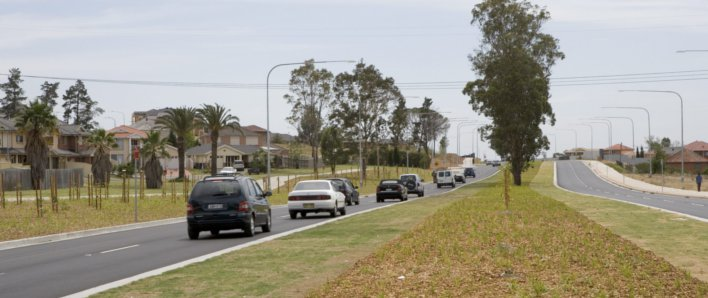 Cowpasture Road after widening works completed, showing two lanes of traffic and a wide central median with grass and trees.