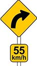 Advisory speed sign showing '55km/h' under a yellow curved right arrow.