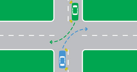 At an intersection and both cars are turning right