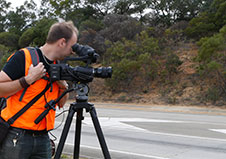Camera operator in high-visibility safety vest filming from the side of the road.