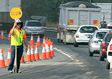 Road worker in high-visibility safety vest holding a 'slow' sign at the side of a road where a lane has been closed due to roadworks.