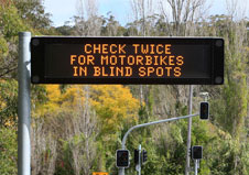 Electronic variable message at the side of a road sign showing the text 'Check twice for motorbikes in blind spots'.