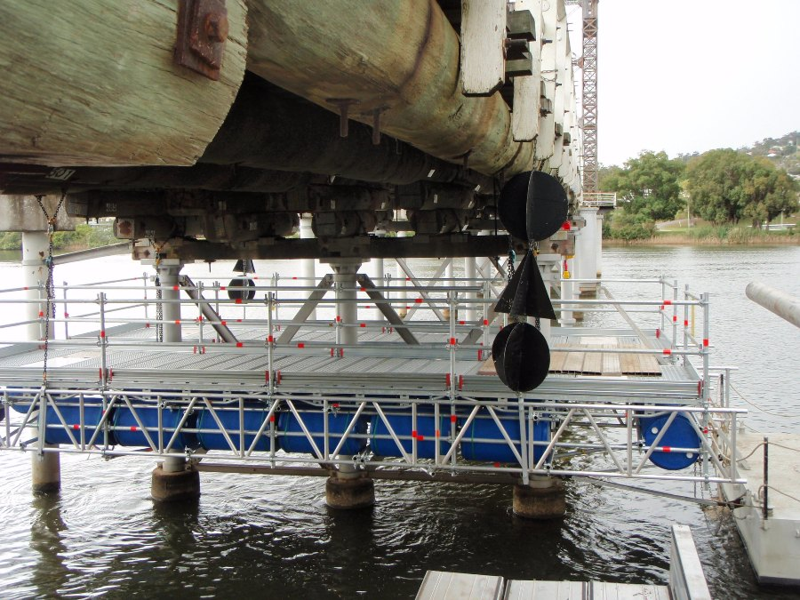 Suspended scaffold - floated into position and lifted into place in each span for below deck works